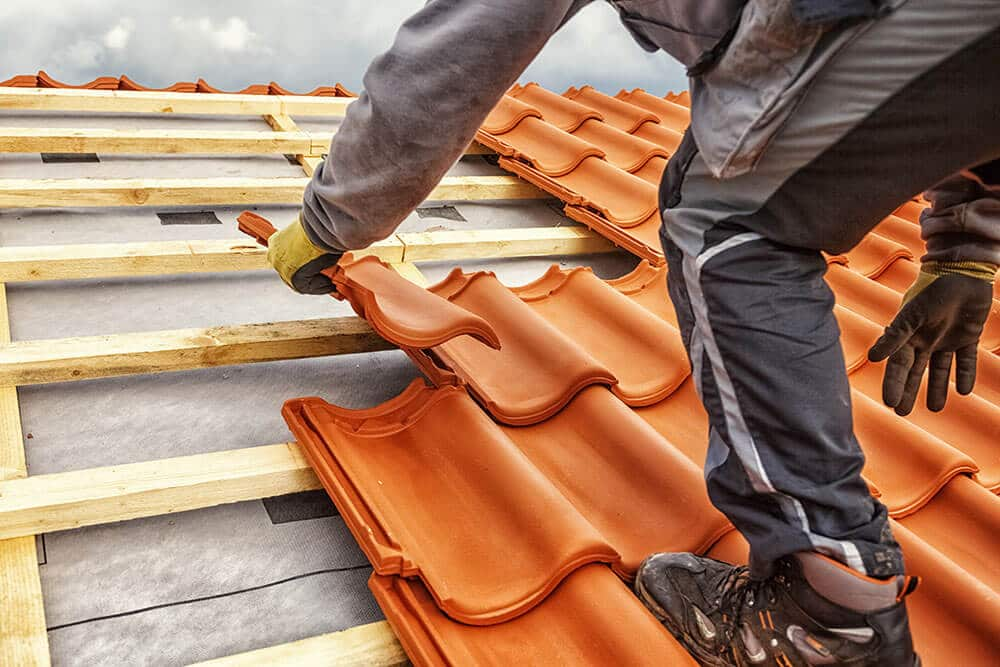 Roofer at work, installing clay roof tiles