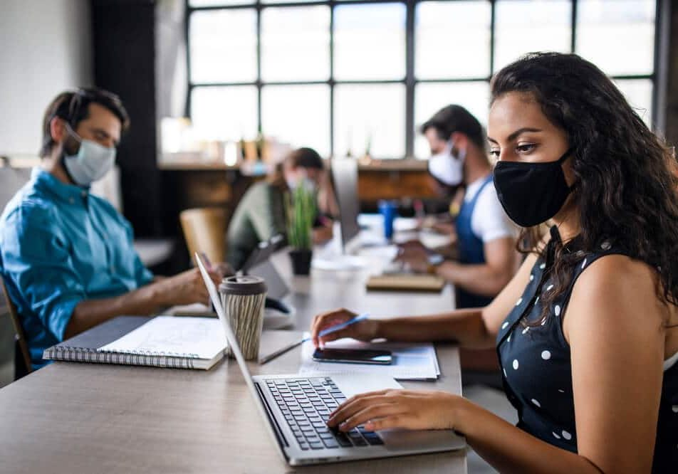 Business people with face masks indoors in office